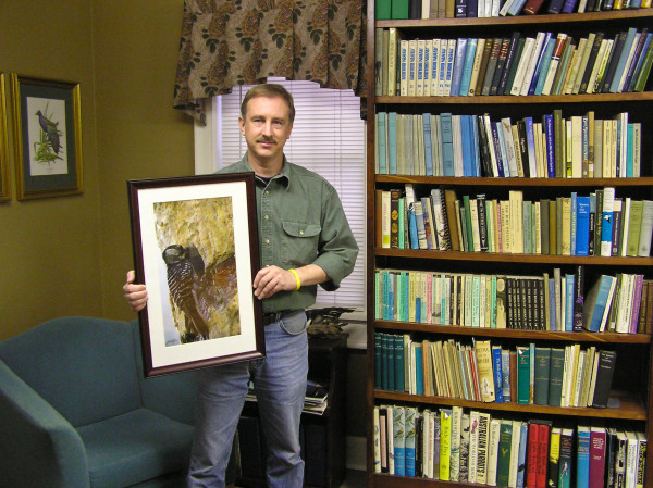 Dana Bradshaw holds framed red-cockaded woodpecker photo within the Paul Baker Library at CCB. Photo by Bryan Watts.