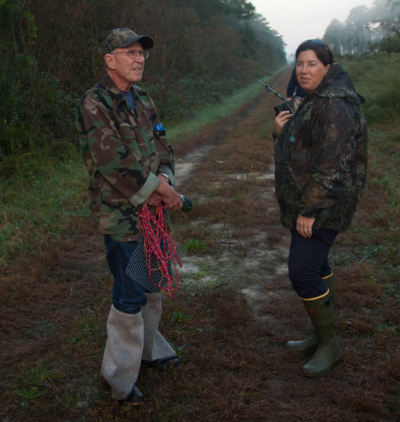 Joe Davis (left) and Lauren Mowbray (right) wait along the road to be picked up after successfully releasing woodpeckers in the swamp at dawn. Photo by Bryan Watts.