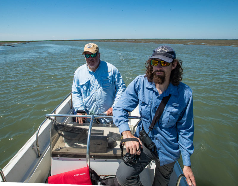 Bart Paxton and Chance Hines survey whimbrels on a boat