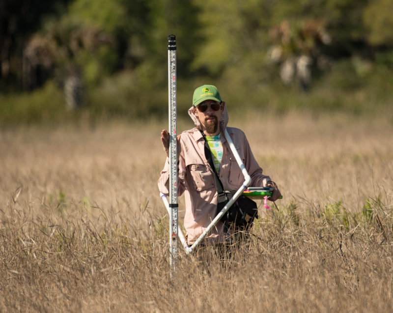 Chance Hines holds a vernier scale within a FL wetland.